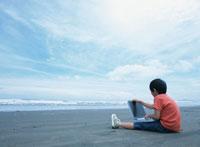 砂浜に座りノートパソコンを操作する日本人の男の子