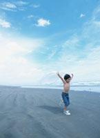 海岸で白いタオルをなびかせて走る日本人の男の子