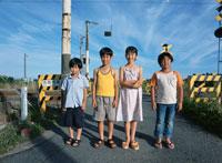 踏切の前で並ぶ子供たち 日本人