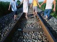 手をつなぎ線路を歩く4人の子供たちの後姿