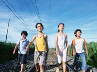 線路を歩く4人の子供たち 日本人