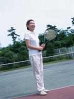 テニスラケットを抱えた中高年女性 日本人
