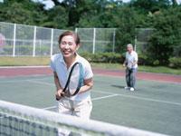 テニスをする中高年夫婦