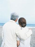 砂浜で寄り添う中高年夫婦の後姿 日本人 02299001543| 写真素材・ストックフォト・画像・イラスト素材|アマナイメージズ