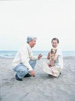 砂浜で犬の散歩をする中高年夫婦 日本人