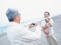 犬の写真を撮る中高年夫婦 日本人