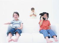 ソファで電話をかける2人の女の子