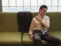 ソファーで肩を揉む外国人ビジネスマン