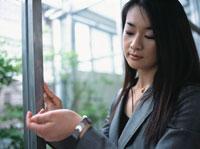 窓辺にて腕時計を見る日本人ビジネスウーマン
