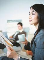カップを持ち雑誌を読む日本人ビジネスウーマン横顔