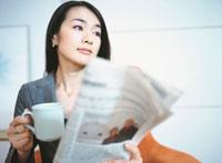 カップを手に新聞を読む日本人ビジネスウーマン