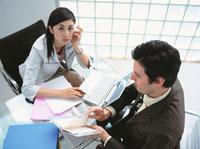 座る日本人ビジネスウーマンと手帳を見る外国人ビジネスマン