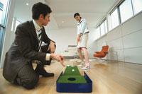 ゴルフパターをする日本人ビジネスウーマンと外国人ビジネスマン 02299001792| 写真素材・ストックフォト・画像・イラスト素材|アマナイメージズ