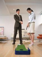ゴルフパターをする日本人ビジネスウーマンと外国人ビジネスマン
