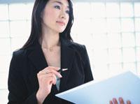 オフィスでファイルを開く日本人ビジネスウーマン