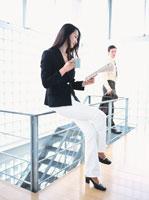 手すりに腰掛ける日本人ビジネスウーマンと外国人ビジネスマン 02299001800| 写真素材・ストックフォト・画像・イラスト素材|アマナイメージズ
