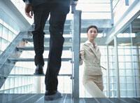 階段を上がる日本人ビジネスウーマンとビジネスマン