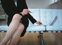 ソファーで足を組みパソコンを操作するビジネスウーマン