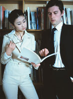 本棚の前で打ち合わせをするビジネスマン&ウーマン