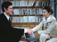 本棚の前で握手をするビジネスマン&ウーマン