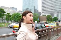 歩道で携帯をかける日本人ビジネスウーマン