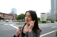 道端で携帯をかける日本人ビジネスウーマン