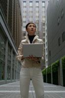 歩道でパソコンを持つ日本人ビジネスウーマン