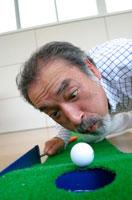 穴に入る直前のゴルフボールを吹く日本人男性