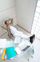 デスクに足を乗せて休息する中高年の日本人男性