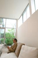ソファーで新聞を読む中高年の日本人男性
