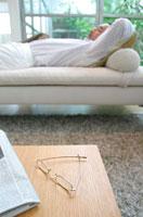 ソファーで寝る中高年の日本人男性と置かれた眼鏡