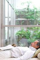 ソファーで寝る中高年の日本人男性と庭の植物
