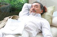 ソファーで寝る日本人の中高年男性