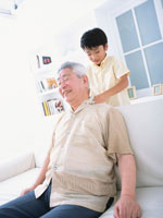 ソファーに座る老人とマッサージする男の子 日本人