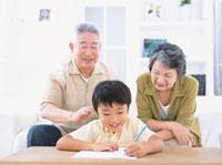 勉強する男の子とソファーに座る老夫婦 日本人