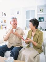ソファーでお茶を飲む日本人老夫婦