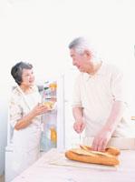 フランスパンを切るおじいさんに話し掛けるおばあさん 日本人