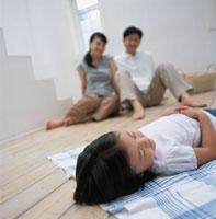 眠る女の子を見つめる両親 日本人