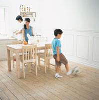 買物袋を開くお母さんと料理するお父さんとボールで遊ぶ男の子