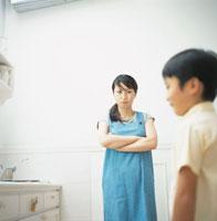 キッチンにて腕組をするエプロン姿のお母さんと横向きの男の子 02299002058| 写真素材・ストックフォト・画像・イラスト素材|アマナイメージズ