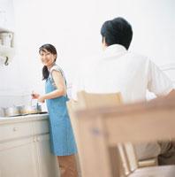 料理しながら振り返る女性と椅子に座る男性 日本人