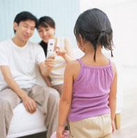 女の子を携帯カメラで撮影するお父さんとお母さん 日本人