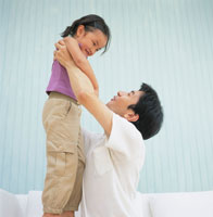 女の子を抱き上げるお父さん