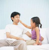 ソファーでお父さんの鼻を指差す女の子 日本人 02299002078| 写真素材・ストックフォト・画像・イラスト素材|アマナイメージズ