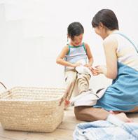 洗濯物を畳むお母さんと女の子 日本人