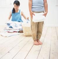 洗濯物を畳む女性と女の子の下半身 日本人