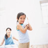 洗濯物を畳むお母さんとタオルを頬に寄せる女の子 日本人
