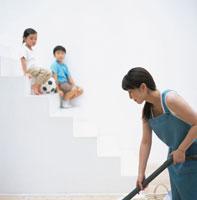 掃除をするお母さんと階段に座る男の子と女の子 日本人