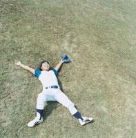 芝生に寝転ぶグローブをはめた野球少年 日本人