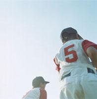 2人の野球少年の後姿と空 02299002255| 写真素材・ストックフォト・画像・イラスト素材|アマナイメージズ